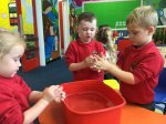 Washing our hands after reading the story 'Golcha dy ddwylo'.